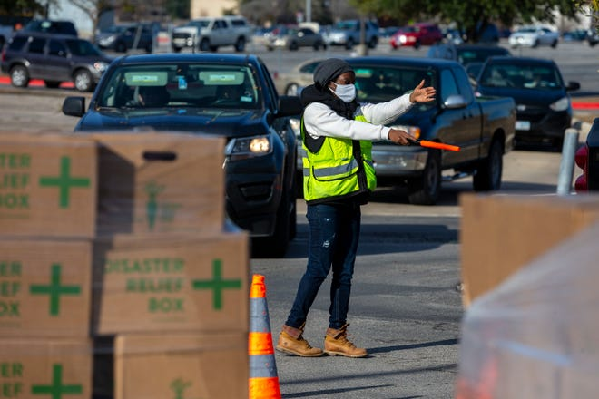 Volunteer Fadia Joseph directs traffic as cars snake through Lehman High School parking lot on Dec. 12 in Kyle for a mass food distribution hosted by the Central Texas Food Bank and city of Kyle. Those in line received assorted produce, milk, and a protein box.