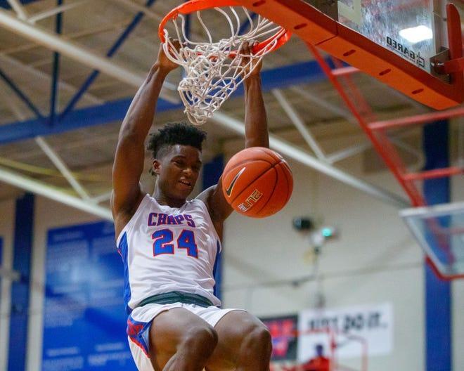 Incoming Kansas freshman basketball guard KJ Adams (24) hangs on the rim after a dunk for Westlake High School in Austin, Texas, last December.
