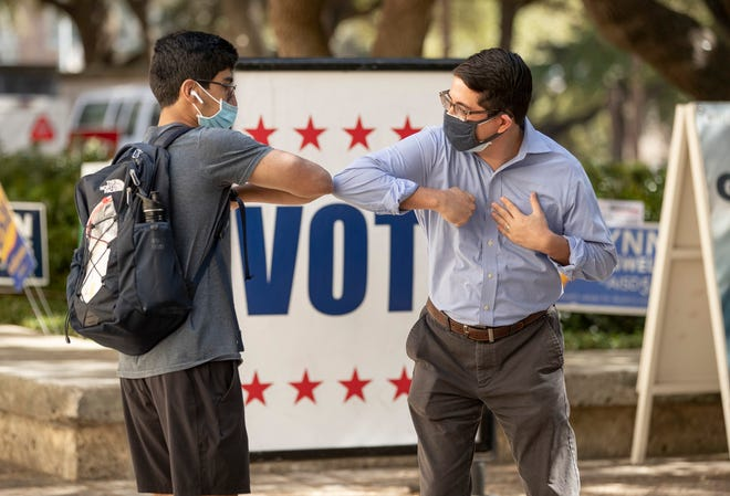 Jose Garza, right, meets a University of Texas student on Election Day. Garza was elected Travis County district attorney.