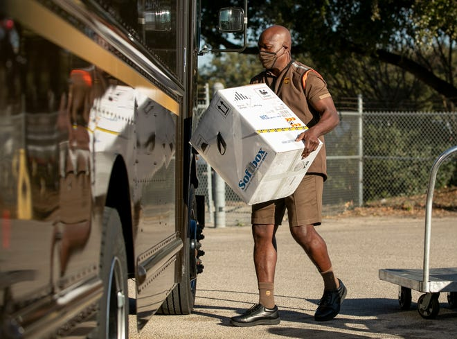United Parcel Service driver Cornelious Littlejohn loads a box with 5,000 doses of the Pfizer coronavirus vaccine Thursday at a UPS distribution center on Tuscany Way in Austin. He was delivering them to the Dell Seton Medical Center.