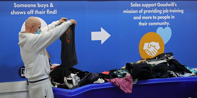 A customer looks through donated clothing Thursday at the Goodwill store on East Waterloo Road in Akron. The Akron-based Goodwill received a $5 million donation from philanthropist MacKenzie Scott.