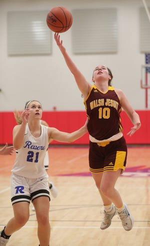 Walsh Jesuit's Maddie Pietrowski drives past Revere's Audrey Livesay during a recent game. The Warriors have won 10 of their past 12 games are 14-5 this season. [Phil Masturzo/ Beacon Journal]
