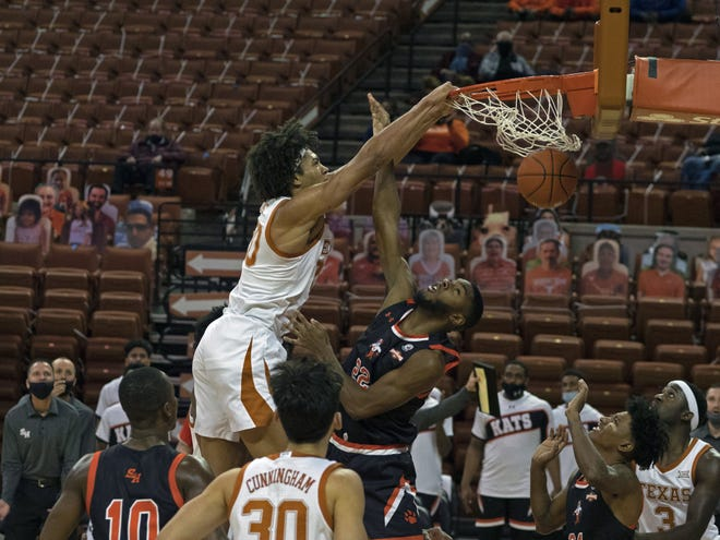Texas forward Jericho Sims dunks over Sam Houston State's Dylan Robertson during the Longhorns' 79-63 win Wednesday night at the Erwin Center.