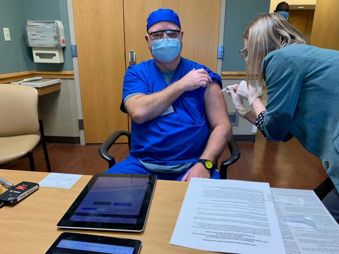 Respiratory therapist Michael Mann holds up his sleeve Wednesday as he receives the first dose of Pfizer's two-part COVID-19 vaccination at Aultman Alliance Community Hospital.