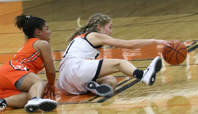 Marlington's Maria Warner, right, continues to dribble the ball as she gets up off the floor and continues to play defended by Massillon's Anny Berry during action at Marlington High School on Wednesday, December 16, 2020.