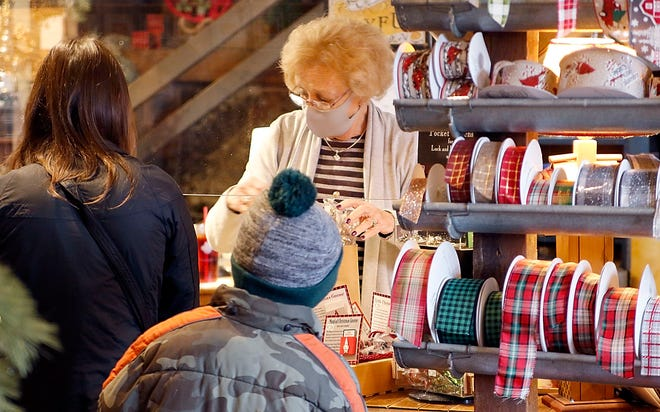 Sally Dilgard checks out customers at her store, The Parsley Pot, behind plexiglass and wearing a face-covering in Ashland. Ashland County avoided going to a Level 4 public emergency on Thursday after appearing on the watch list last week. TOM E. PUSKAR/TIMES-GAZETTE.COM