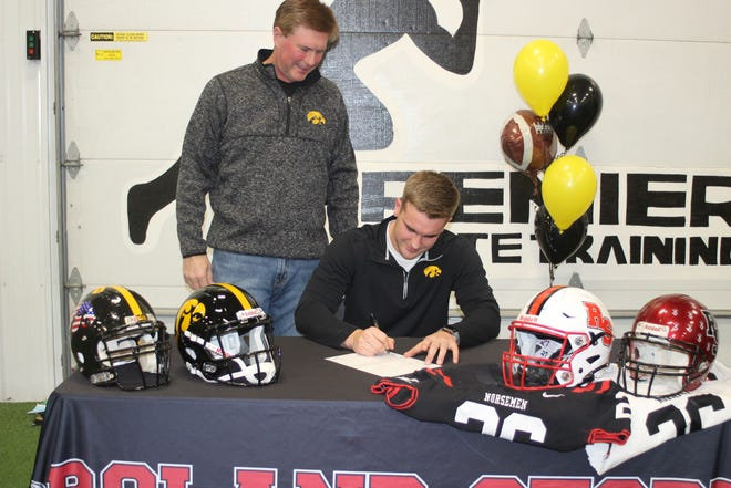 Roland-Story senior Zach Twedt signs a letter of intent to play Division 1 football at the University of Iowa as his father, Seth Twedt, looks on at Premier Athlete Training in Ames Wednesday.