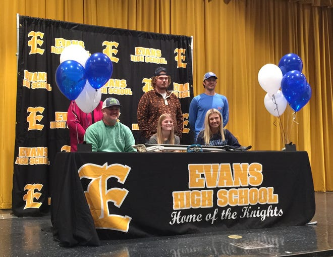 Evans High School senior Camryn Barrow (center) signs a national letter of intent to play lacrosse at Chowan University on Thursday in the EHS auditorium.