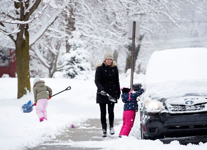Jill Jansto clears snow from her car with help from her daughters, Chloe, 5 and Aubrey, 2, in Beaver.