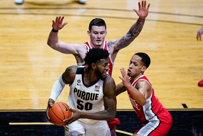 Purdue forward Trevion Williams (50) is defended by Ohio State guard CJ Walker (13) and forward Kyle Young (25) during the second half of an NCAA college basketball game in West Lafayette, Ind., Wednesday, Dec. 16, 2020. (AP Photo/Michael Conroy)