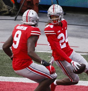 Ohio State cornerback Shaun Wade (24) celebrates with defensive end Zach Harrison after returning an interception for a touchdown against Indiana on Nov. 21.