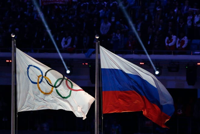 The Russian national flag, right, flies after it is hoisted next to the Olympic flag during the closing ceremony of the 2014 Winter Olympics in Sochi, Russia. The Court of Arbitration for Sport ruled Thursday that Russia will not be able to use its name or flag at the next two Olympics due to its participation in a state-ordered scheme to tamper with anti-doping test results.