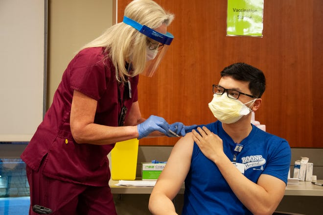 Dr. Linh Le receives an inoculation from nurse Robyn Carter on Thursday at Boone Hospital Center.