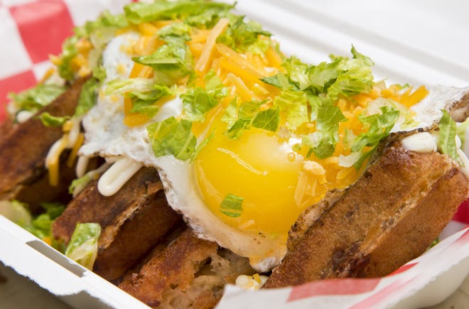 The Empire waffle is made with breakfast sausage and topped with a sunny-side up egg and shredded cheddar.