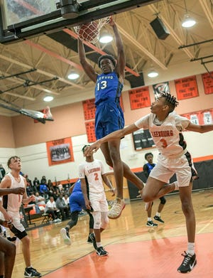 Wildwood's Joe Poyser (13) dunks against Leesburg during Wednesday's game at the Lake and Sumter County boys basketball tournament at Leesburg High School. Poyser helped to lead the Wildcats to a 71-59 win against the Yellow Jackets.  [PAUL RYAN / CORRESPONDENT]