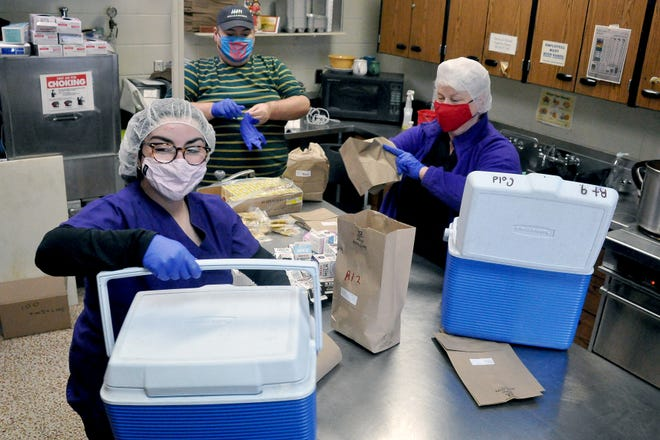 Sarah, Matthew and Sally Fusek pack 104 hot meals plus several frozen entrees at the Wooster Community Center to be distributed to Meals on Wheels recipients. On Thursday the meal was chicken chili, a corn muffin, baked apples, juice and a lemon cookie.