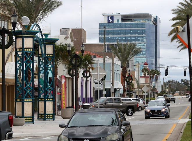 The new 11-story headquarters for Brown & Brown looms in the distance along Beach Street in downtown Daytona Beach Thursday, Dec. 17, 2020. The national insurance brokerage has begun moving its senior management team into the office tower at 300 N. Beach St.  with hundreds more teammates set to move in early January 2021. The hundreds of workers the new headquarters will bring to the area are expected to provide a big boost to downtown restaurants and shops.