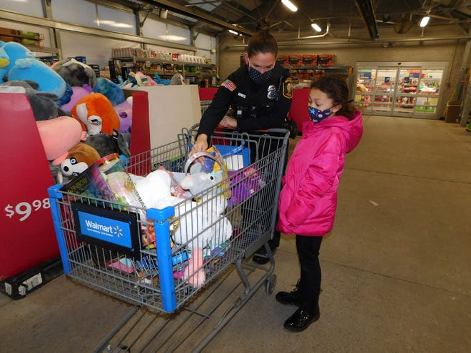Mariah Seelbach, 7, takes another look at her selections with Mohawk Police Officer Ashley Jones before reaching the checkout counter at Herkimer Walmart on Wednesday, Dec. 16, 2020. Police officers from Mohawk, Ilion and Herkimer took turns shopping with children from their local communities during the Shop with a Cop event.