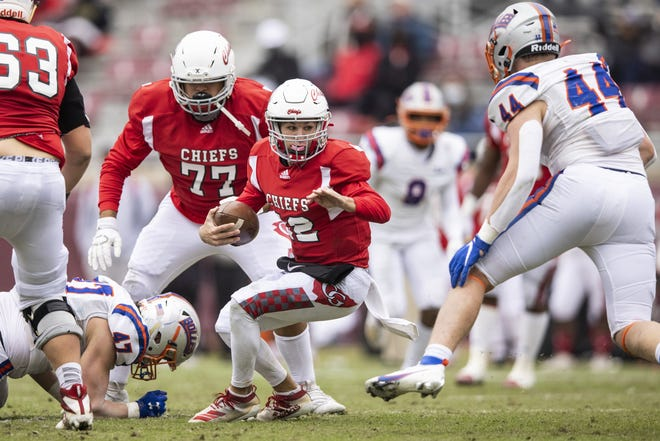 Cardinal Gibbons quarterback Brody Palhegyi (12) scrambles during the Class 4A State Championship football game against Bolles at Doak Campbell Stadium.