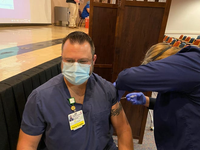 Registered nurse Patrick Purcell gets a COVID-19 vaccine Thursday at Memorial Hospital in Jacksonville.