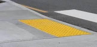 "A ""Detectable Warning Device"" on a sidewalk curb ramp."