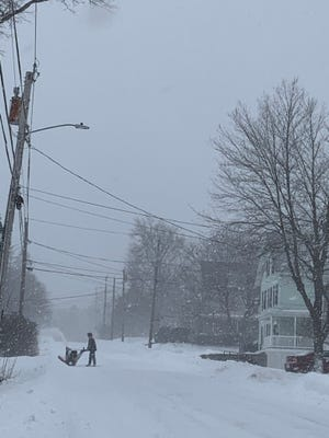 A Gardner resident clears a driveway on Prospect Street during the winter storm that hit the area on Thursday, Dec. 17.