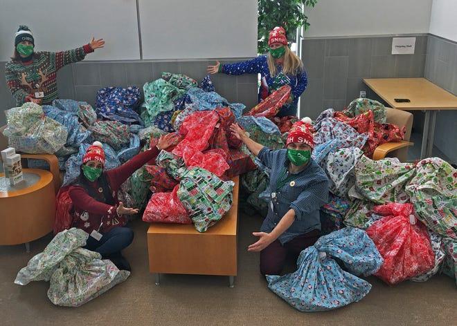 Voluntários do Plano de Saúde do Neighborhood de Rhode Island embrulhando os presentes para serem distribuídos por crianças carenciadas daquele estado.