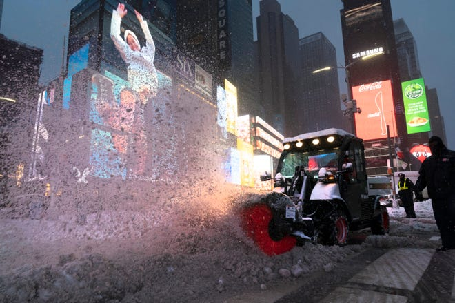 A tractor with a power brush clears snow Thursday in New York's Times Square. (AP Photo/Mark Lennihan)