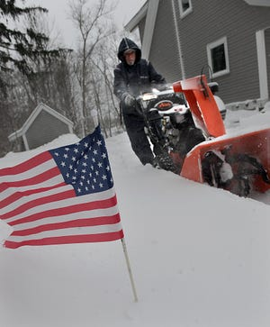 Patriotism has no limits, as Buddy Santosuosso clears snow with his snowblower on Dilla Street in Milford on Thursday, Dec. 17, 2020. Milford was among the hotspots as of midday Thursday, accumulating more than a foot of snow.