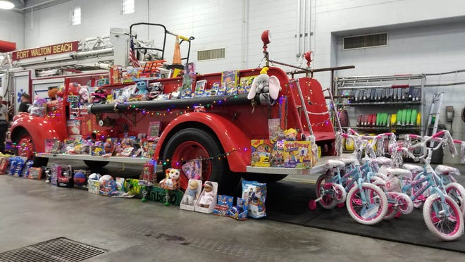 """Fort Walton Beach Fire Department's historic Engine 1 sits covered in toys on Sunday, the first day of the department's """"Santa's Firehouse Toy Drive Cruz Thru."""" The event continues Saturday and Sunday from 11 a.m. to 3 p.m. at the main station at 5 Hollywood Blvd."""