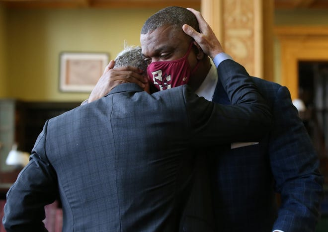Serge Georges, Jr. hugs college friend Robert Bruhl, who flew in from Hawaii for the ceremony, before being sworn in by Gov. Charlie Baker as an Associate Justice of the Supreme Judicial Court during a ceremony at the State House on Wednesday, Dec. 16.