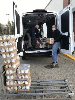 Mark Jago, left, the executive director of Community Outreach Services, and David Higham, the organization's food programs manager, load canned goods into a van in preparation for the COS Holiday Food Basket Program.