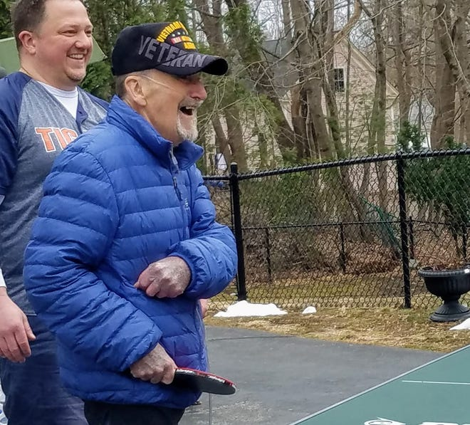 Wearing his typical outfit, a Vietnam Veteran hat and blue jacket, David Weston of Kennebunk, Maine, plays ping pong in March 2020. He passed away with COVID-19 on Sunday, Dec. 13, at age 80, his family said.