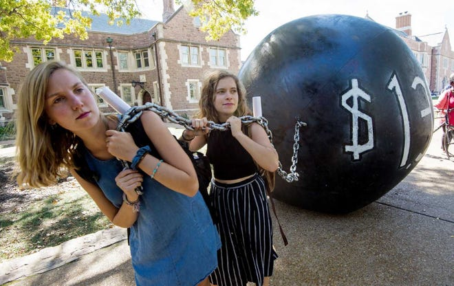 Students pulling a heavy ball representing the total outstanding student debt in the U.S. at over $1.5 trillion.