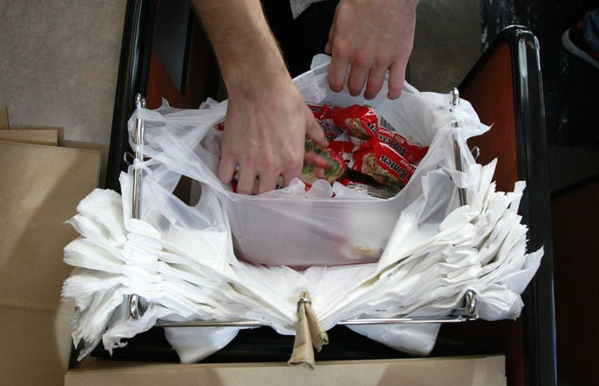 A clerk bags groceries in plastic  bags. The Gainesville City Commission attempted to ban plastic bags from certain uses in the city, but the Legislature passed preemption legislation that overturned the ban.