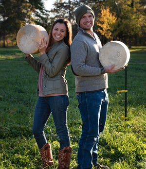 Rebecca and John Oravets hold wheels of cheese at Old Forge Dairy. The handcrafted cheese is made at their farm in Rootstown.
