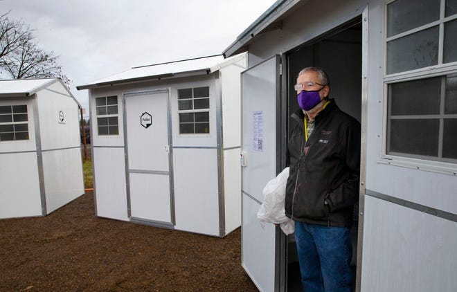 Dan Bryant, executive director of SquareOne Villages, stands in the doorway of a Pallet shelter after it was dropped off at a location near Roosevelt Boulevard in Eugene.