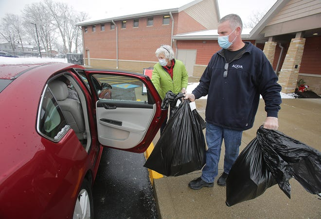 Massillon Salvation Army volunteers Sarah Leffler and Todd Wachtel carry out presents to families waiting in their vehicles during the organization's annual Christmas assistance giveaway. More than 1,400 area people benefited this holiday season.