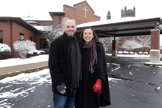 The Revs. J.R. and Amy Rozko in the parking lot of the First Church of the Resurrection in Canton.