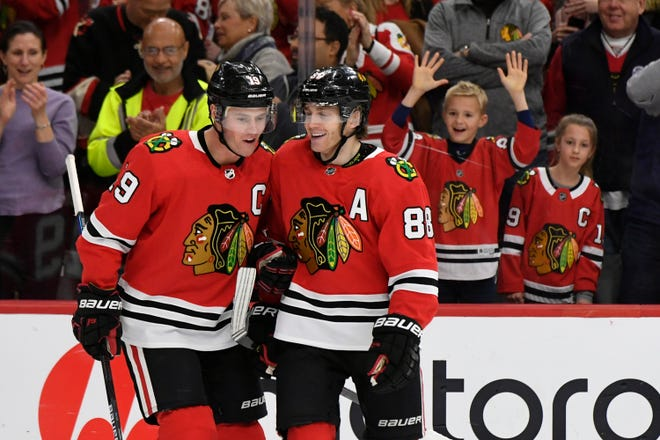 Chicago Blackhawks star Patrick Kane (88) celebrates with teammate Jonathan Toews (19) after scoring a hat trick during the third period against the Minnesota Wild on Dec. 15, 2019, in Chicago. The team is going to remain the Blackhawks, according to CEO Danny Wirtz. Speaking publicly Thursday for the first time since baseball's Cleveland Indians announced Monday they plan to change their name, Wirtz reiterated the franchise's commitment to the Blackhawks team name.