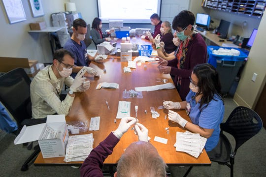 SwedishAmerican pharmacists and technicians assemble doses of the Pfizer-BioNTech COVID-19 vaccine at SwedishAmerican hospital in Rockford, Ill..