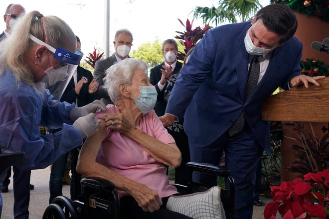 Florida Gov. Ron DeSantis asks Vera Leip, 88, how she feels after receiving Pfizer's COVID-19 vaccine in December 2020 in Pompano Beach.