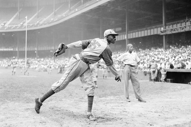 In this Aug. 2, 1942, file photo, Kansas City Monarchs pitcher Leroy Satchel Paige warms up at New York's Yankee Stadium before a Negro League game between the Monarchs and the New York Cuban Stars.