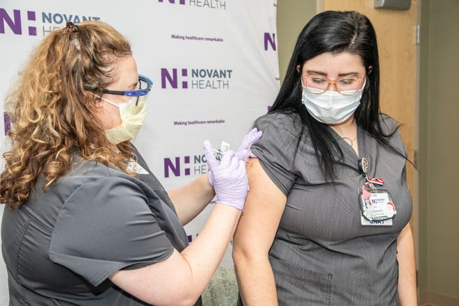Madison Valenza receives the first COVID-19 vaccine at Novant Health Brunswick Medical Center in Bolivia.