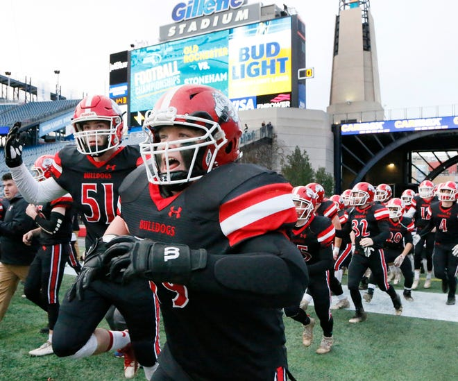 Old Rochester players run onto the field prior to the start of the Division 6 Super Bowl game against Stoneham at Gillette Stadium in Foxboro.