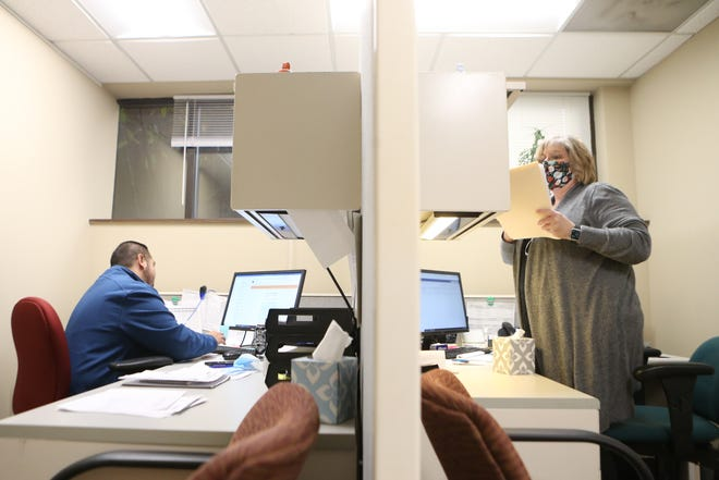 Working from their cubicles at Express Employment Professionals, 2300 S.W. 29th St., recruiters Jordan Barron and Sharon Miller help match job seekers with potential employers Wednesday afternoon.