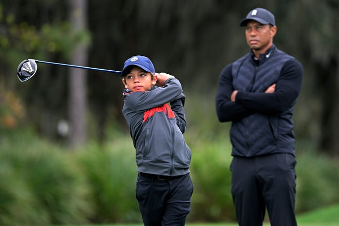 Tiger Woods, right, watches as his son Charlie tees off on the 12th hole during a practice round of the Father-Son Challenge in Orlando, Florida.