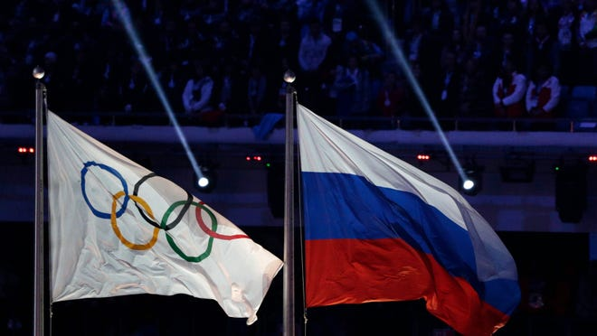 The Russian national flag, right, flies after it is hoisted next to the Olympic flag during the closing ceremony of the 2014 Winter Olympics in Sochi, Russia.