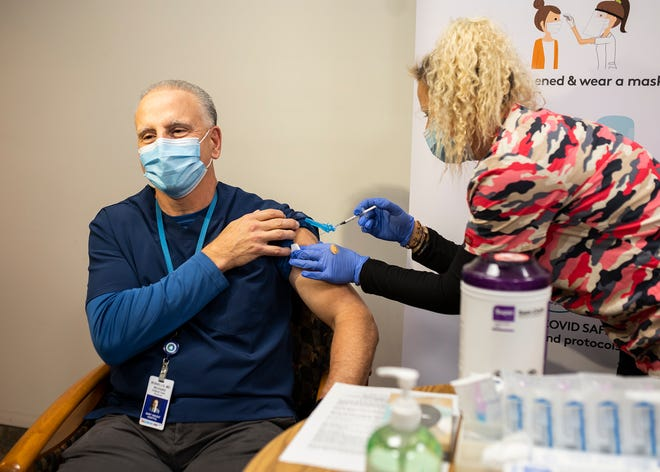 Physician Richard Rosiello receives a COVID-19 vaccine from Privia Parzych at St. Vincent Hospital in December.