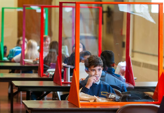 Students eat lunch behind a clear barrier in the cafeteria at Saint Mary School in Shrewsbury in September.  [T&G Staff/Rick Cinclair]